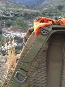 A survival bandana in blaze orange tied to my pack