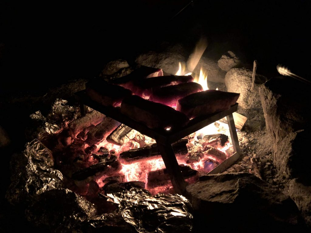 steaks over a camp fire